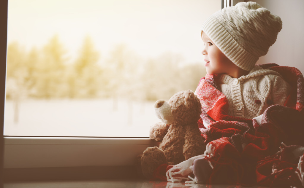 child little girl with  teddy bear at window